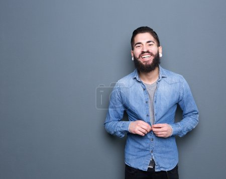 Photo pour Portrait d'un jeune homme séduisant avec la barbe souriant et boutons de réglage sur la chemise - image libre de droit