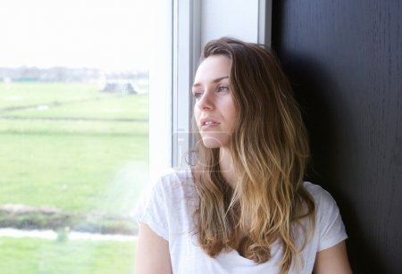 Photo for Close up portrait of a young woman looking outside through window - Royalty Free Image
