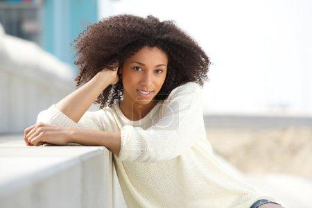 Photo pour Close up portrait of a beautiful young african woman smiling outdoors - image libre de droit