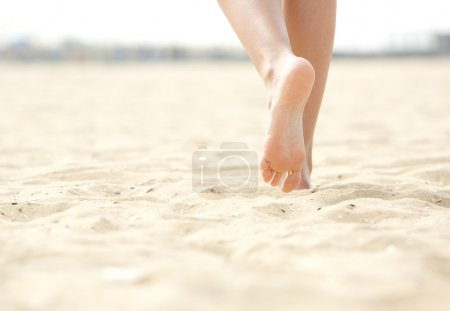 Photo for Close up low angle woman barefoot walking on beach - Royalty Free Image