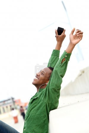 Man smiling with arms raised and mobile phone
