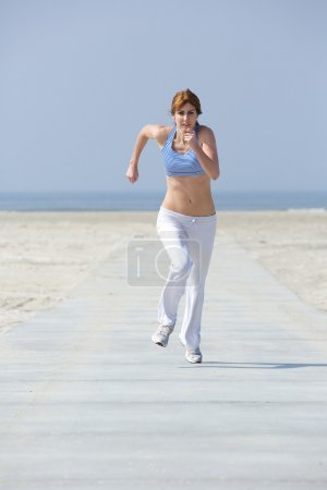 Mature woman jogging at the beach