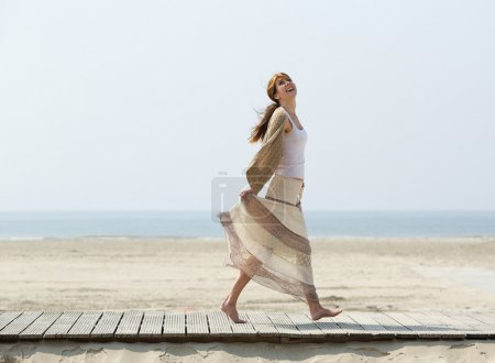 Photo for Full length portrait of a carefree middle aged woman walking barefoot at the beach - Royalty Free Image
