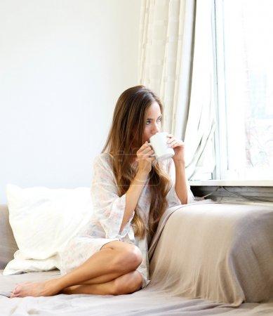 Photo pour Gros plan portrait d'une belle jeune femme buvant du café le matin et regardant par la fenêtre - image libre de droit
