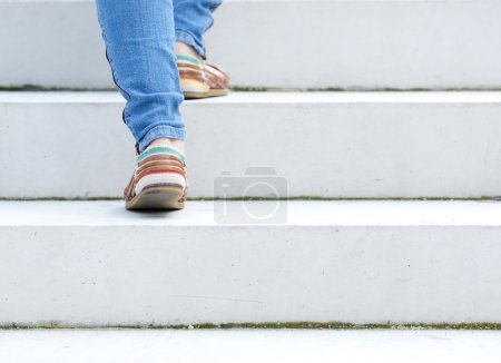 Photo for Female walking upstairs on stone staircase outdoors - Royalty Free Image