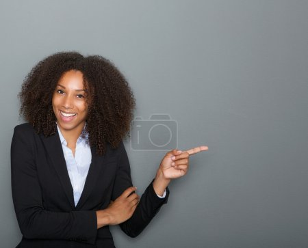 Smiling business woman pointing finger