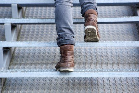 Photo for Close up rear view of man walking up stairs in boots - Royalty Free Image
