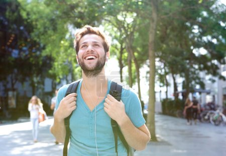 Photo for Close up portrait of a handsome young man walking outdoors with backpack - Royalty Free Image