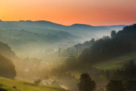 Photo pour Village dans les montagnes au petit matin brouillard - image libre de droit