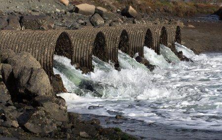 Photo pour Des eaux d'inondation déchaînées s'écoulent à travers six grands tuyaux de ponceaux industriels - image libre de droit