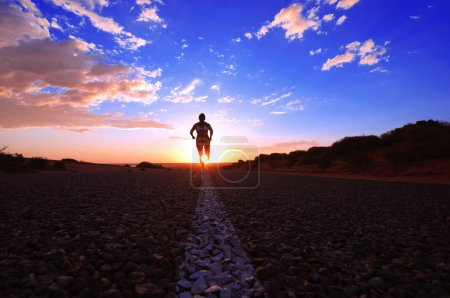 Photo for Female Runner running along a remote road in the Australian Outback, Western Australia - Royalty Free Image
