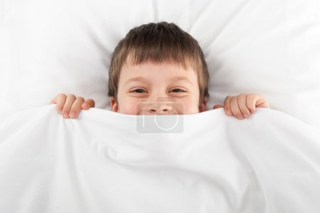 cheerful boy in bed