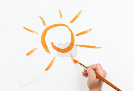 watercolor painted sun and child hand with brush