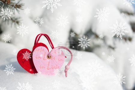 Photo for Red hearts toy in snowfall on fir tree - Royalty Free Image