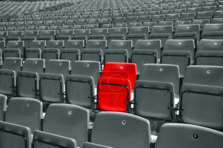 Photo for Black and white picture of stadium seat with only one red - Royalty Free Image