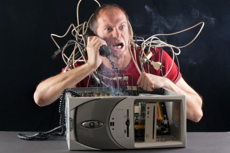 Photo for Man having his computer burning phoning technical support for help - Royalty Free Image