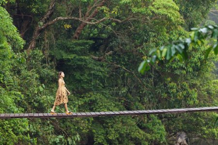 Young woman walking on suspended wooden bridge in ...