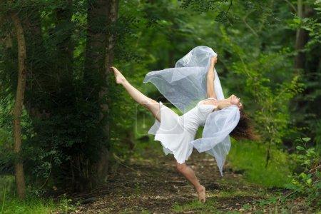 Photo pour Portrait mystique d'une belle femme gracieuse pieds nus dans une robe blanche fraîche avec ses bras drapé en tissu transparent filmy, posant avec une jambe soulevée sur un fond boisé vert luxuriant - image libre de droit
