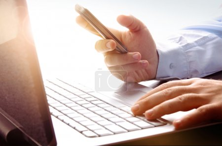 Photo for Photo of businessman using laptop and mobile phone - Royalty Free Image