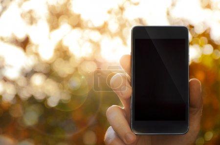 Hand holding smart phone, blurred background