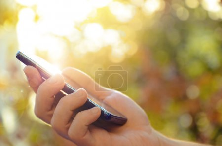 Photo for Man's hand using mobile smart phone, blurred nature background - Royalty Free Image