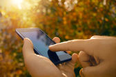 Closeup mužských rukou pomocí smartphonu, přírodní pozadí
