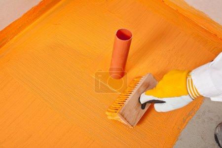 Plumber builder brush applied waterproofing pipe corne