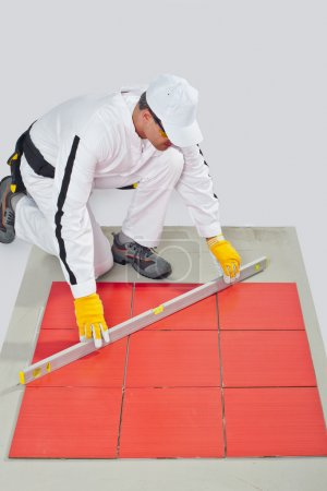 Worker levels Tiles applied on Floor reinforced fiber mesh