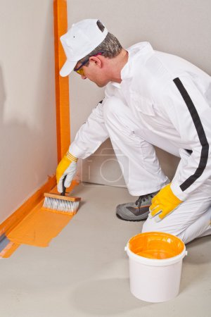 Worker waterproofing around the wall and floor