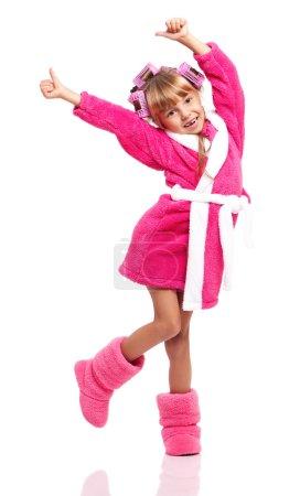 Photo pour Portrait de jolie petite fille en peignoir rose avec bigoudis sur la tête isolé sur fond blanc - image libre de droit