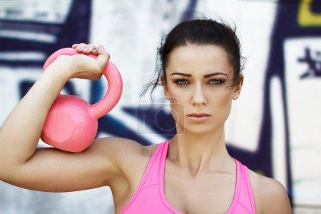 Photo pour Femme tenant une kettlebell rose sur l'épaule, sports de plein air - image libre de droit
