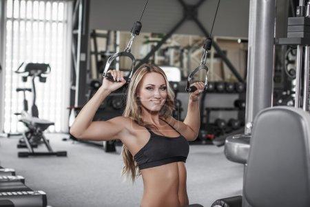 Blonde sexy bodybuilder pulldown practice in gym