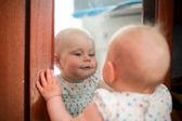 šťastný jeden rok stará holčička vyhledávání vedle zrcadla