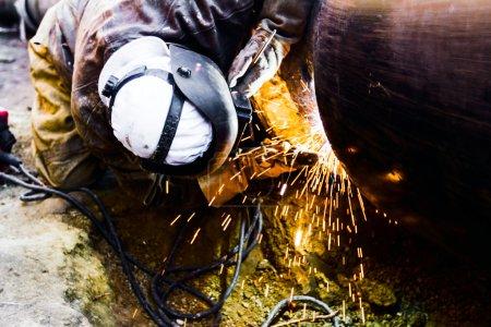 Foto de Soldador trabajando en un oleoducto en construcción usando equipo global y seguridad - Imagen libre de derechos