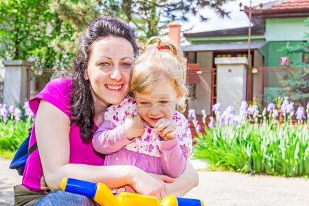 Photo pour Maman et sa fille profiter au soleil du printemps - image libre de droit