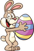 Easter bunny holding a big egg Vector clip art illustration with simple gradients All in a single layer