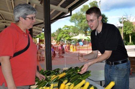 Photo pour Vendeur discutant des recettes de courgettes avec le client à la farmers market - image libre de droit