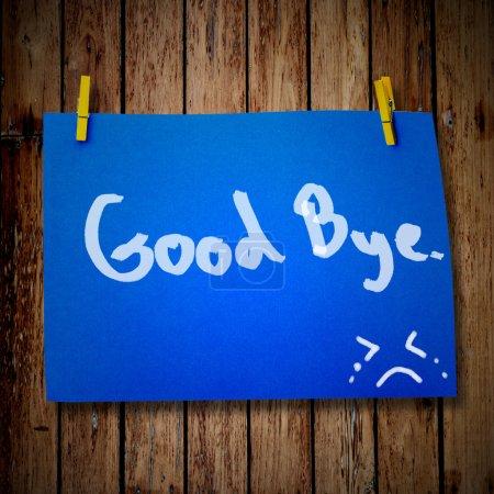 Photo pour Papier au revoir et vêtements peg sur un fond en bois avec sourire visage - image libre de droit