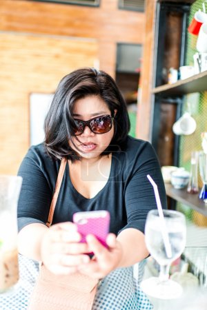 Serious overweight, fat business woman wearing sunglasses with m
