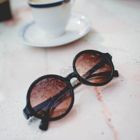 Sunglasses on marble table with a cup of coffee.