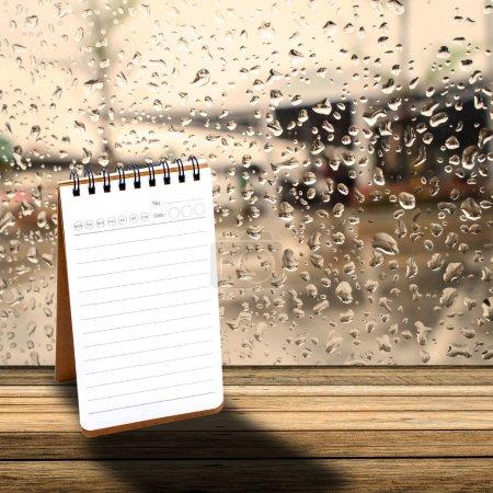 Photo pour Carnet avec fond de fenêtre jour de pluie - image libre de droit