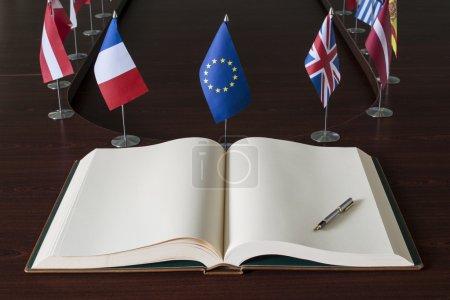 Photo pour Un livre de grande diffusion ouverte, stylo plume et un ensemble de petits drapeaux des pays de l'UE en option - image libre de droit
