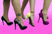 Three pairs of sexy female legs wearing high heels on pink background