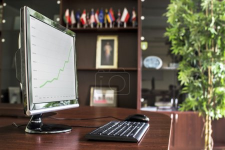Luxury office with desktop PC and ascending chart displayed