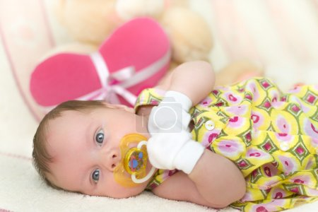 Infant baby girl lying on bed with teddy bear