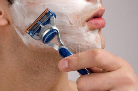 Shaving the beard with a razor.