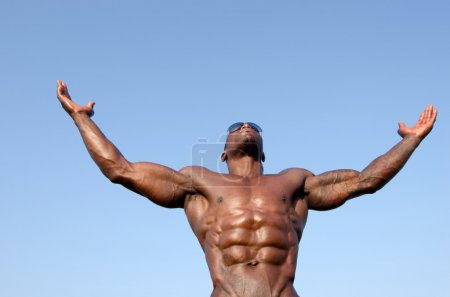 Strong bodybuilder man with perfect abs, shoulders,biceps, triceps and chest posing with sky as background