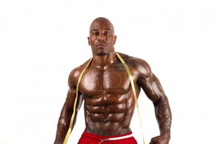 Black bodybuilder taking his muscle measurements with a centimeter. Strong man with perfect muscles. Isolated on white background
