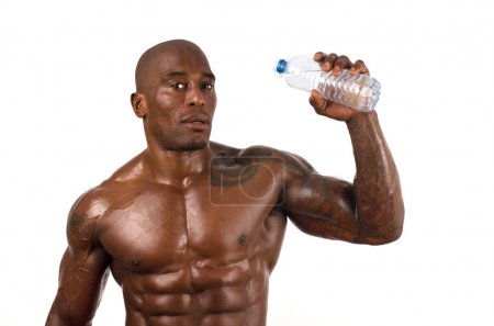 Black bodybuilder drinking water after a hard workout. Strong man with perfect muscles. Isolated on white background.