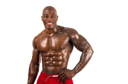 Confident black bodybuilder smiling.Strong man with perfect muscles. Isolated on white background.